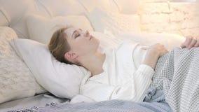 Jeune femme de pensée songeuse s'étendant dans le lit banque de vidéos