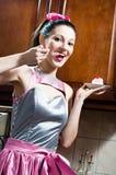 Jeune femme de pin-up de belle brune drôle de fille mangeant le gâteau délicieux à la cuisine ayant l'appareil-photo de sourire d Photographie stock