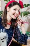 Jeune femme de pin-up drôle avec la machine à coudre et le portrait de sourire de bande et de regard heureux de mesure de plan ra Photos stock