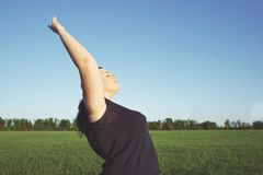 Jeune femme de poids excessif faisant le yoga au pré d'été Photographie stock