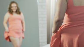 Jeune femme de poids excessif se tenant devant le miroir, satisfaisant avec la réflexion banque de vidéos