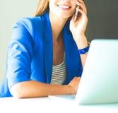 Jeune femme de portrait au téléphone devant un ordinateur portable photographie stock libre de droits