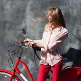 Jeune femme de portrait dans le pantalon en twill rouge tenant des mains sur sa bicyclette rouge de vintage, se tenant contre le  Photographie stock