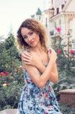 Jeune femme de raffinage dans une robe bleue se reposant contre une roseraie et de vieux bâtiments Le regard est dirigé vers l'ap image stock
