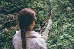 Jeune femme de randonneur appréciant la vue de vallée avec la rivière de montagne Image stock