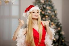 Jeune femme de Santa de beauté près de l'arbre de Noël Lu à la mode Photo libre de droits
