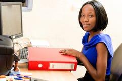 Jeune femme de secrétaire s'asseyant à son bureau Photo libre de droits