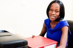 Jeune femme de secrétaire s'asseyant à son bureau Photographie stock libre de droits