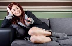 Jeune femme de sofa avec l'extérieur de TV Photo stock