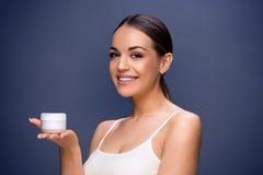 Jeune femme de soins de la peau tenant la crème cosmétique images stock