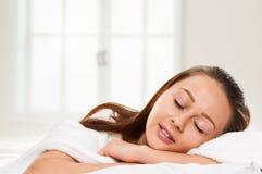 Jeune femme de sommeil dans le lit sur l'oreiller Photographie stock