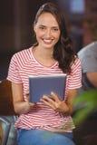 Jeune femme de sourire à l'aide de la tablette Image libre de droits