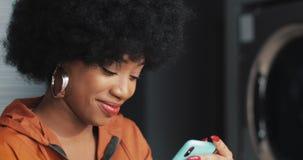 Jeune femme de sourire ? l'aide du smartphone ? la laverie automatique Blanchisserie publique de libre service banque de vidéos