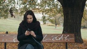 Jeune femme de sourire à l'aide du smartphone se reposant sur le banc dans le parc Beau service de mini-messages européen de fill clips vidéos