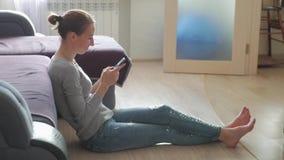 Jeune femme de sourire à l'aide du téléphone portable tout en se reposant sur un plancher à la maison banque de vidéos