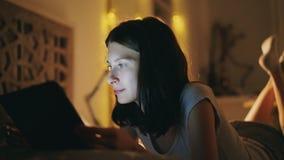 Jeune femme de sourire à l'aide de la tablette pour partager le media social se trouvant dans le lit à la maison la nuit photos libres de droits