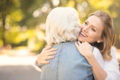 Jeune femme de sourire étreignant la vieille mère en parc Photos stock