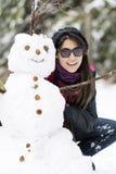Jeune femme de sourire étreignant le bonhomme de neige Photos stock