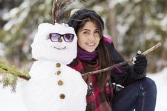 Jeune femme de sourire étreignant le bonhomme de neige Images libres de droits