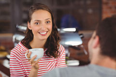 Jeune femme de sourire appréciant le café avec son ami Photos stock