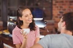 Jeune femme de sourire appréciant le café avec un ami Photos stock