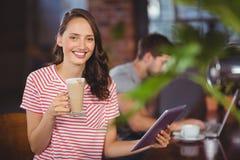 Jeune femme de sourire appréciant le latte et à l'aide de la tablette Photos libres de droits