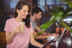 Jeune femme de sourire appréciant le latte et à l'aide de la tablette Photo stock