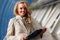 Jeune femme de sourire attirante dans le costume léger tenant le dossier Photo stock