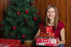 Jeune femme de sourire avec des cadeaux de Noël Image stock