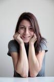Jeune femme de sourire avec des joues se penchant sur des mains Image stock