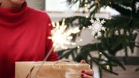 Jeune femme de sourire avec l'arbre de Noël et guirlandes sur le fond tenant des cierges magiques et tenant un cadeau dans elle banque de vidéos