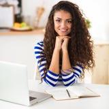 Jeune femme de sourire avec l'ordinateur portable dans la cuisine à la maison photo stock