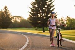 Jeune femme de sourire avec la bicyclette sur la route photographie stock libre de droits