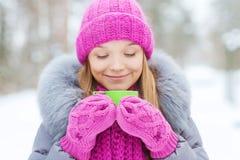 Jeune femme de sourire avec la tasse dans la forêt d'hiver images stock