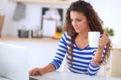 Jeune femme de sourire avec la tasse et l'ordinateur portable de café dans la cuisine à la maison Jeune femme de sourire Photo stock