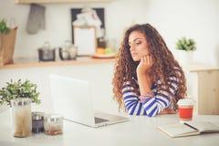 Jeune femme de sourire avec la tasse et l'ordinateur portable de café dans la cuisine à la maison Jeune femme de sourire image stock