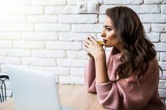 Jeune femme de sourire avec la tasse et l'ordinateur portable de café dans la cuisine à la maison image stock