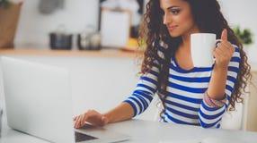 Jeune femme de sourire avec la tasse et l'ordinateur portable de café dans la cuisine à la maison images libres de droits