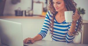 Jeune femme de sourire avec la tasse et l'ordinateur portable de café dans la cuisine à la maison photo stock