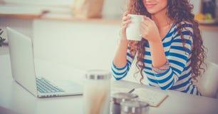 Jeune femme de sourire avec la tasse et l'ordinateur portable de café dans la cuisine à la maison image libre de droits