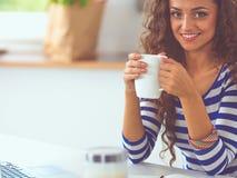 Jeune femme de sourire avec la tasse et l'ordinateur portable de café dans la cuisine à la maison images stock