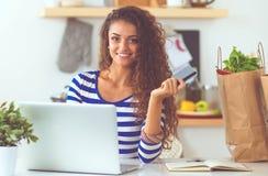 Jeune femme de sourire avec la tasse et l'ordinateur portable de café dans la cuisine à la maison photographie stock libre de droits