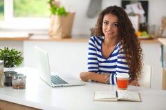 Jeune femme de sourire avec la tasse et l'ordinateur portable de café dedans Images stock