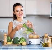Jeune femme de sourire avec le brocoli photographie stock libre de droits