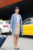 Jeune femme de sourire avec le sac de voyage au-dessus du taxi Photo stock
