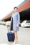 Jeune femme de sourire avec le sac de voyage au-dessus du taxi Photo libre de droits