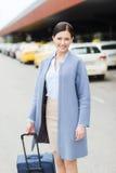 Jeune femme de sourire avec le sac de voyage au-dessus du taxi Image stock