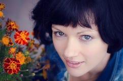 Jeune femme de sourire avec le souci de fleurs images stock