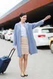 Jeune femme de sourire avec le taxi contagieux de sac de voyage Images libres de droits