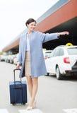 Jeune femme de sourire avec le taxi contagieux de sac de voyage Images stock